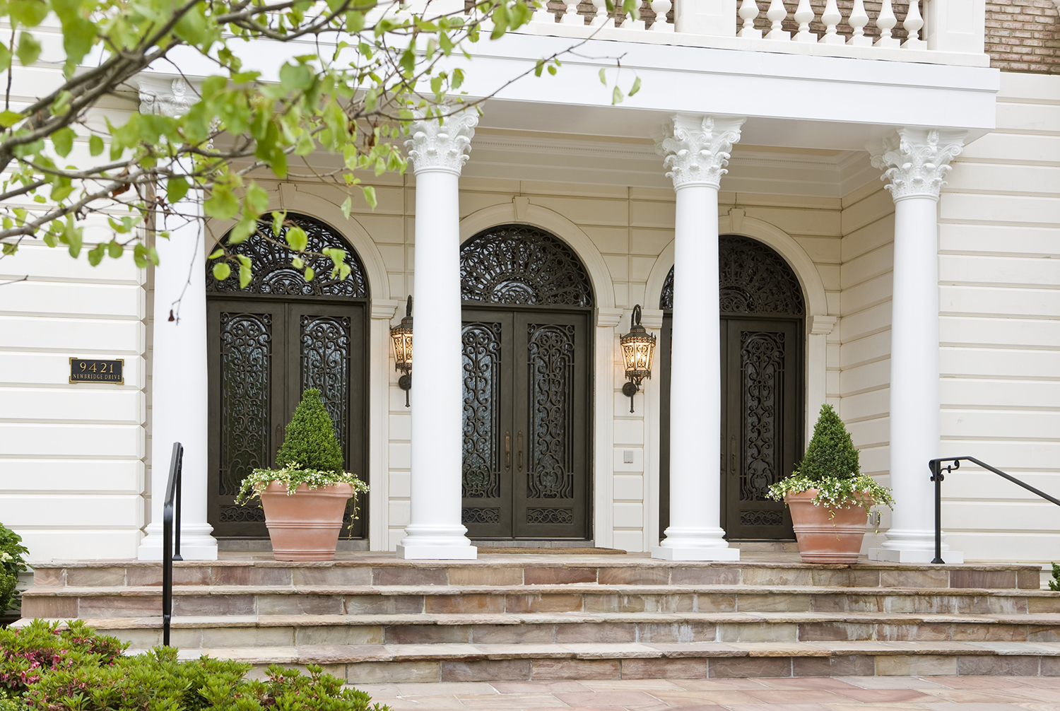 The entrance of a home with 4 white columns and three front doors.