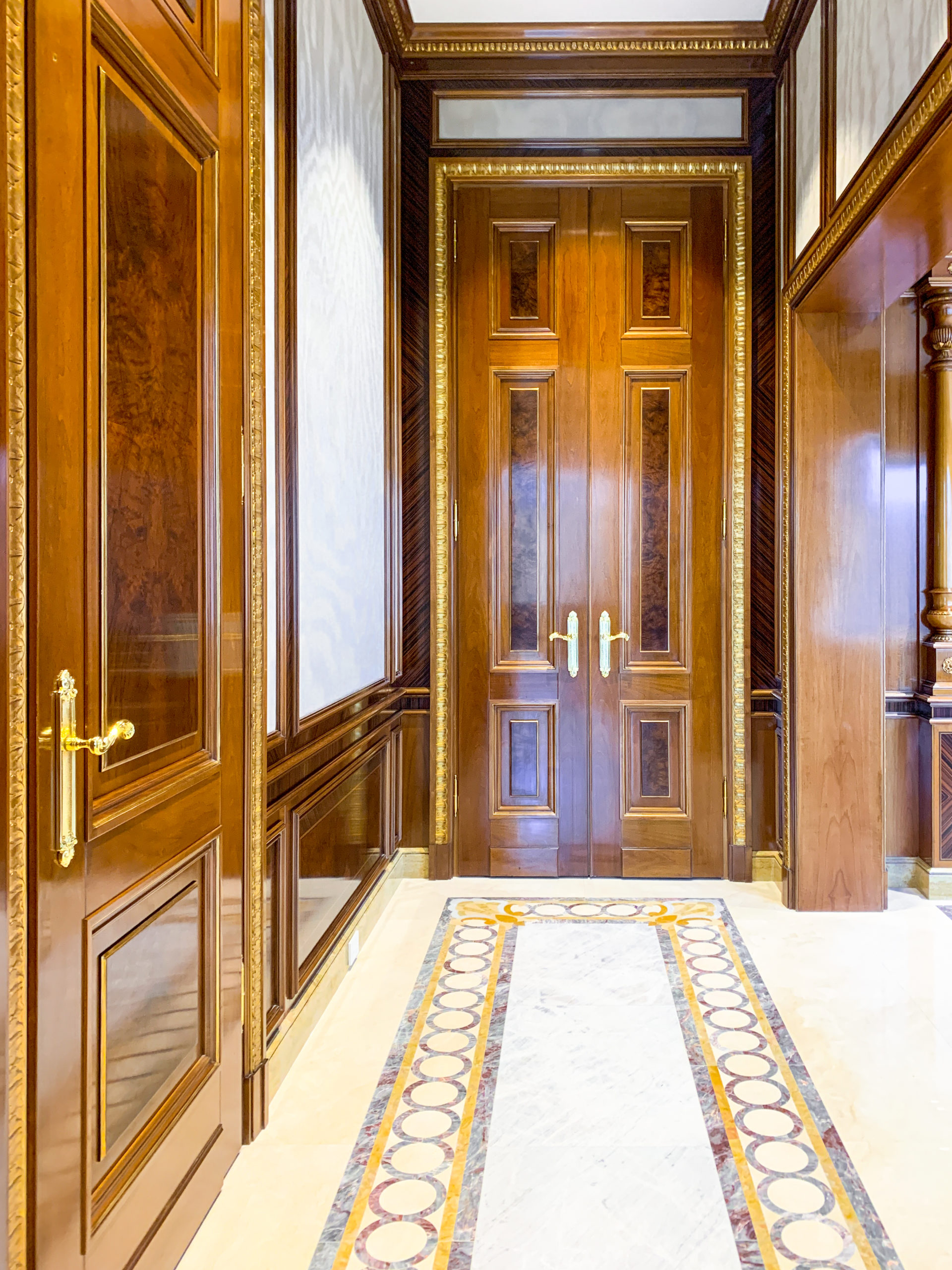 Foyer and Elevator with custom wood paneling and flooring