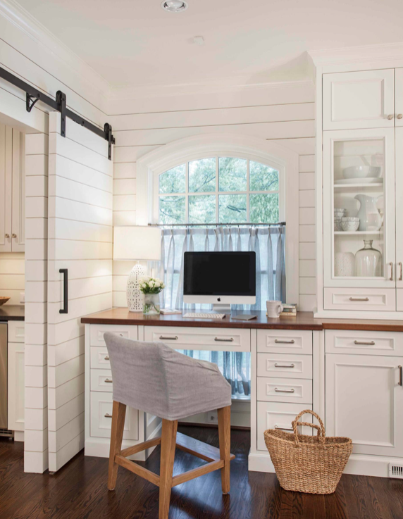 Home office with white built-in shelves and desk